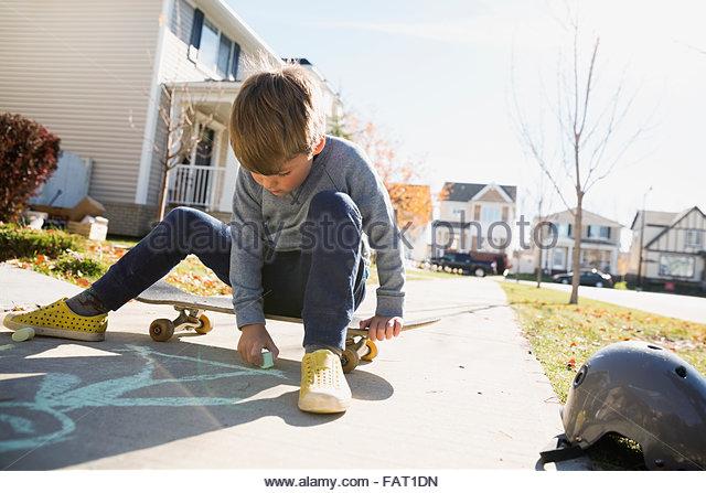 Junge mit Skateboard auf Bürgersteig mit Kreide zeichnen Stockbild