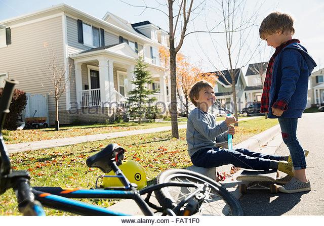 Brüder mit Rad- und Gehweg an Nachbarschaft Bordsteinkante Stockbild
