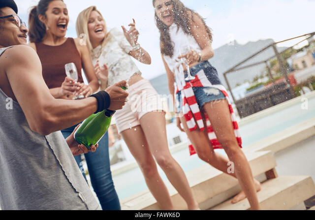 Party Bild der junge Mann eine Flasche Champagner zu öffnen. Frauen stehen ein Swimmingpool halten Gläser Stockbild