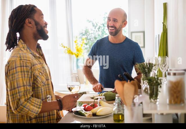 Smiley homosexuelles Paar Weintrinken in Küche Stockbild