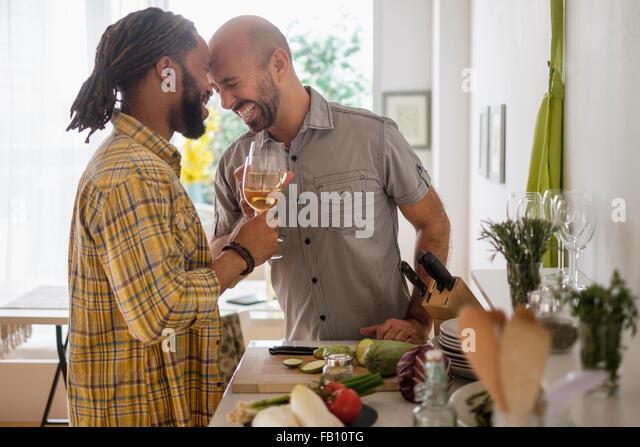 Smiley homosexuelles Paar Weintrinken in Küche - Stock-Bilder