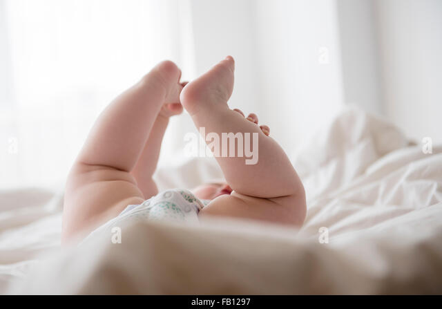 Babymädchen (12-17 Monate) mit Beinen oben liegend Stockbild