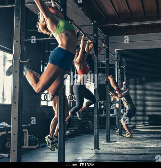 Reihe von Menschen, die auf Übung Bar im Fitness-Studio trainieren Stockbild