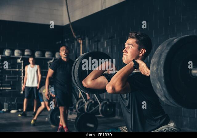 Mann und Trainer Ausbildung mit Langhantel in Turnhalle Stockbild