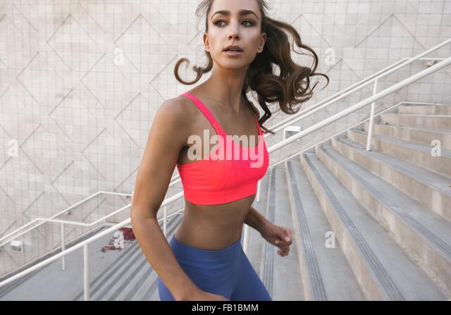 Junge Frau trägt Sport-BH laufen, Treppensteigen, wegschauen Stockbild