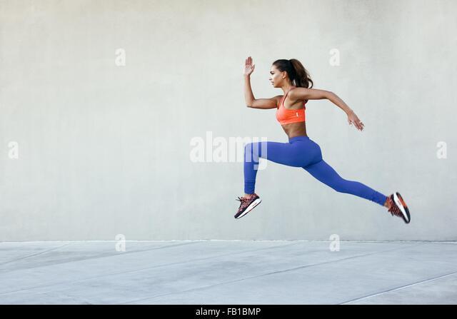 Seitenansicht der junge Frau trägt Sportkleidung in der mittleren Luft schreitende Haltung Stockbild