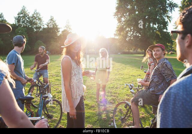 Gruppe der Partei gehen Erwachsene Ankunft im Park auf Fahrräder bei Sonnenuntergang Stockbild