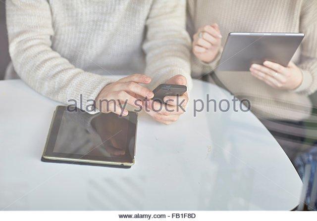 Junger Mann und Frau sitzen am Tisch, mit digitalen Tablet und Smartphone, Mittelteil Stockbild
