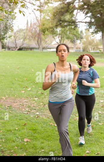 Vorderansicht der Trägerinnen Sportbekleidung energetisch auf Rasen laufen Stockbild