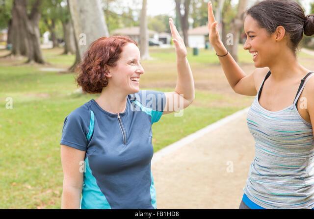 Junge Frauen tragen Sportbekleidung von Angesicht zu Angesicht lächelnd dabei hohe fünf Stockbild