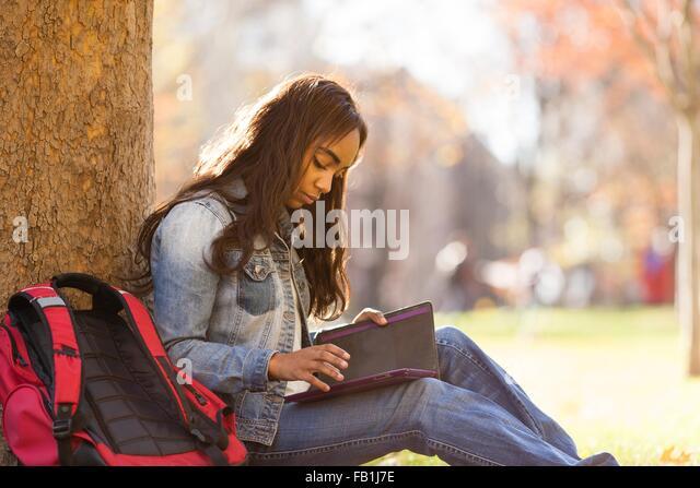 Seitenansicht der junge Frau sitzend gelehnt Baum blickte auf digital-Tablette Stockbild