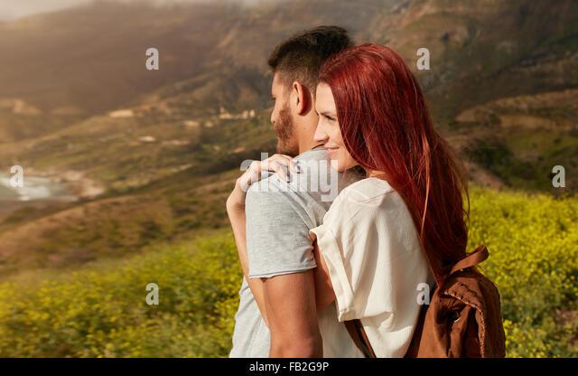 Romantische junges Paar genießen Sie die Sehenswürdigkeiten beim Wandern durch die Berge. Junge Frau umarmte Stockbild