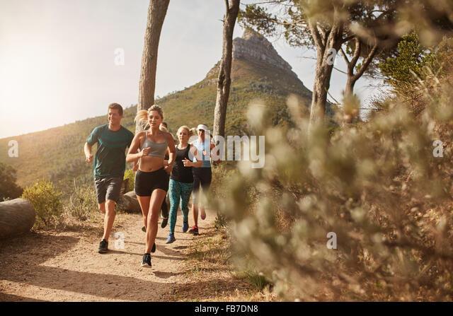 Gruppe von jungen Erwachsenen training und laufen gemeinsam durch Wanderwege am Hang im Freien in der Natur. Fit Stockbild