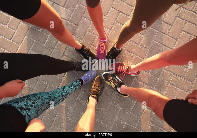 Beine der Athleten tragen Sportschuhe in einem Kreis. Draufsicht der Läufer zusammenstehen. Stockbild
