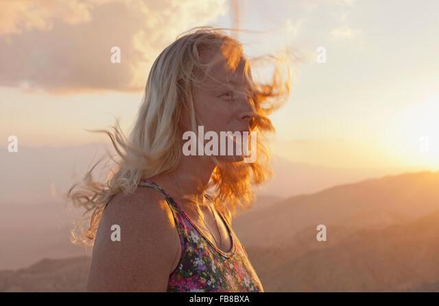 USA, California, Joshua Tree National Park, weibliche Touristen Entspannung in Berglandschaft bei Sonnenuntergang - Stock-Bilder
