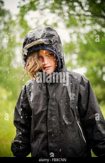 Schweden, Uppland, blondes Mädchen (8-9) in Regenmantel Stockbild