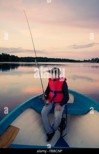 Västervik, Schweden, Smaland, Tjust Archipel Hasselo, Boy (10-11) Fliegenfischen in Boot auf See Stockbild