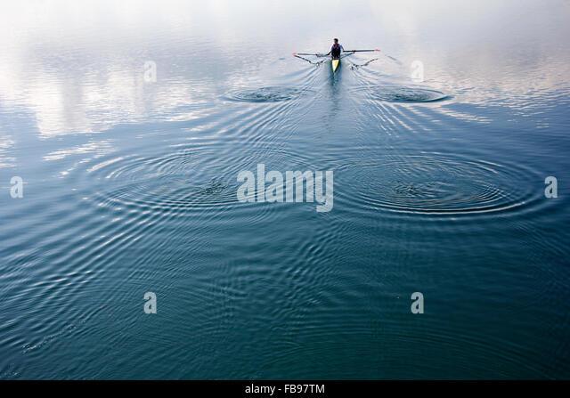 Junger Mann in einem Boot rudern auf dem ruhigen See Stockbild