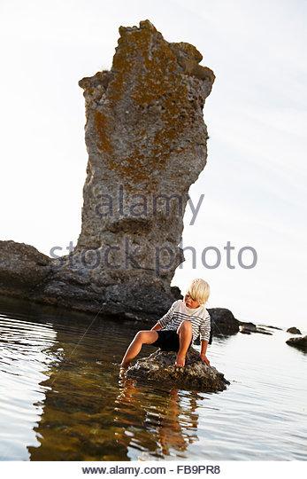 Schweden, Gotland, Faro, Blonde junge (2-3) auf Felsen mit einem Bein im Wasser sitzen Stockbild