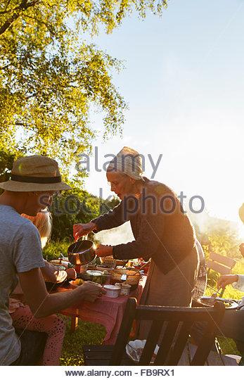 Schweden, Sodermanland, Jarna, Familie mit Kleinkind (4-5) mit Abendessen im Hinterhof bei Sonnenuntergang Stockbild