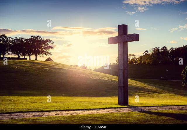 Schweden, Sodermanland, Stockholm, Gamla Enskede, Skogskyrkogarden, Kreuz im grünen Tal bei Sonnenuntergang Stockbild