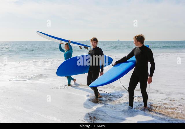 Portugal, Lissabon, drei Menschen, die Surfbretter am Strand Stockbild