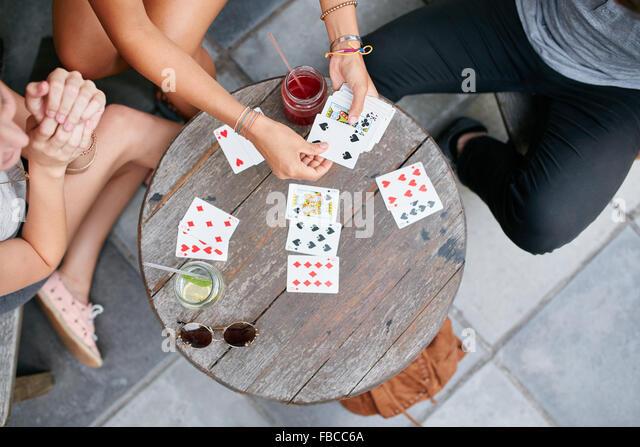Draufsicht der drei jungen Freunde Spielkarten im Café. Die Jugendlichen spielen Kartenspiel im Coffee Shop. Stockbild