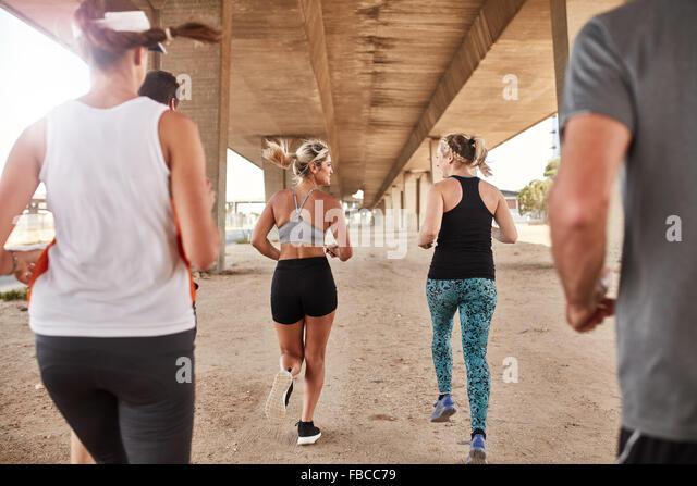 Porträt der Gruppe von Läufern in Fitness Kleidung laufen unter einer Brücke. Junge Männer und Stockbild