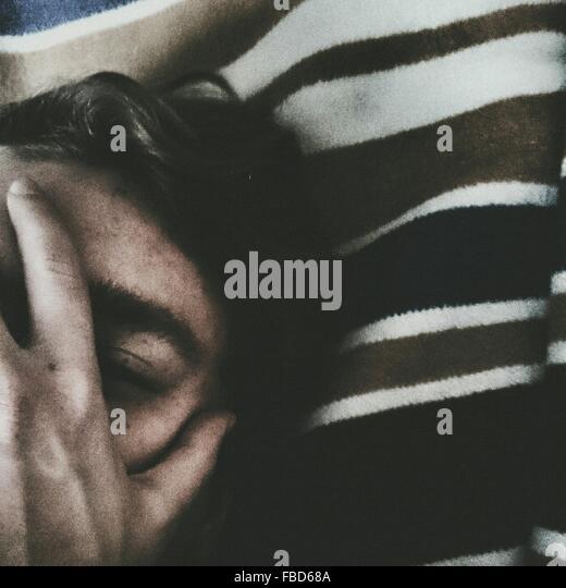 Zugeschnittenes Bild des Mannes bedeckte sein Gesicht während Sie gemütlich auf Bett Stockbild
