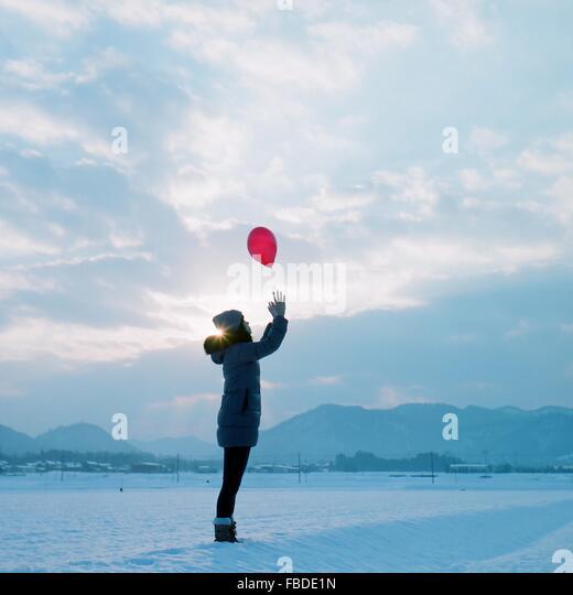 Seitenansicht des Mädchens In warme Kleidung fangen roten Ballon während auf verschneiten Feld stehen Stockbild