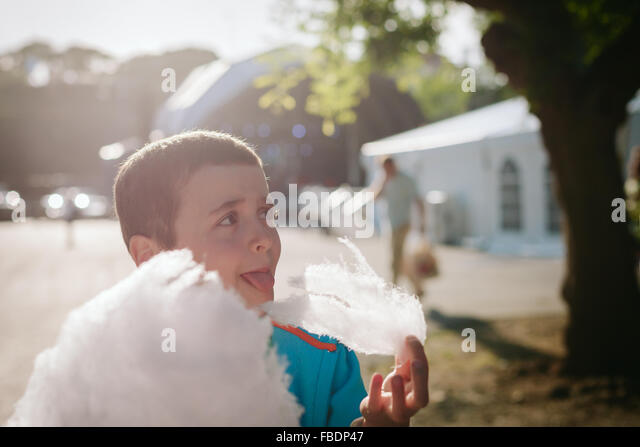 Junge essen Zuckerwatte an sonnigen Tag Stockbild