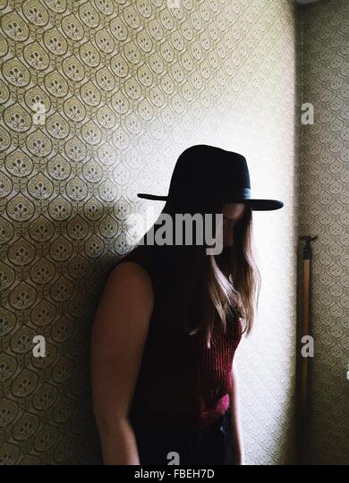 Seitenansicht der Frau mit Hut stehen gegen die Wand beim Blick nach unten Stockbild