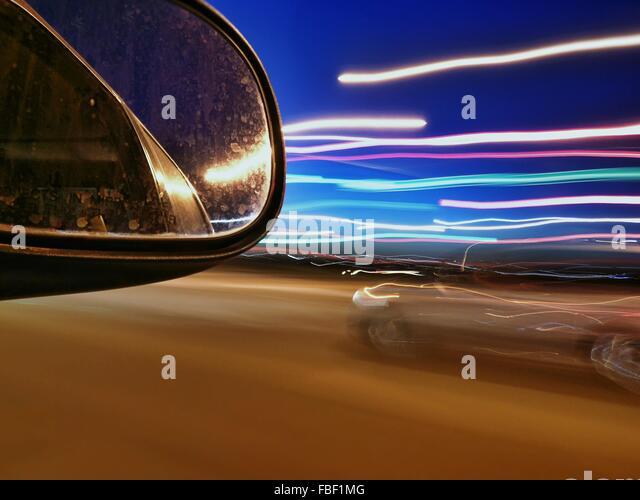 Außenspiegel und Licht-Strecken auf der Straße bei Nacht Stockbild