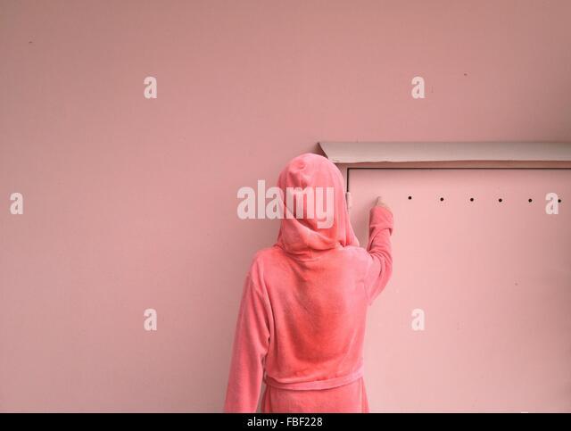 Rückansicht der Frau In der Haube Rosa Wand Stockbild