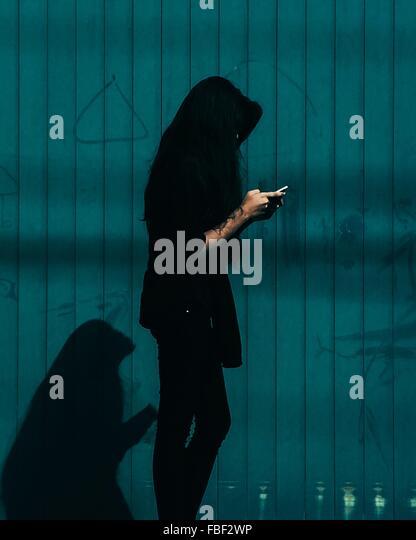 Frau mit Smartphone gegen blaue Wand - Stock-Bilder
