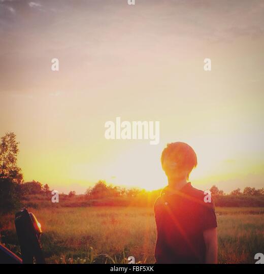 Hinterleuchtete Mann steht im Feld während des Sonnenuntergangs Stockbild