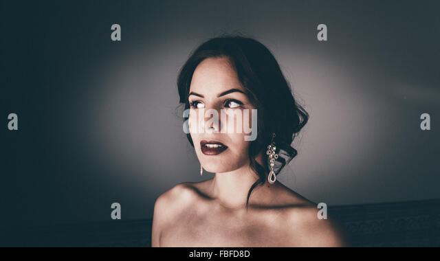 Schöne nachdenkliche Frau wegschauen gegen Wand Stockbild