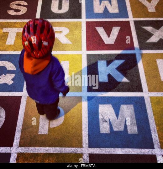 High Angle View Of Kind stehend auf gemalte Alphabete Stockbild