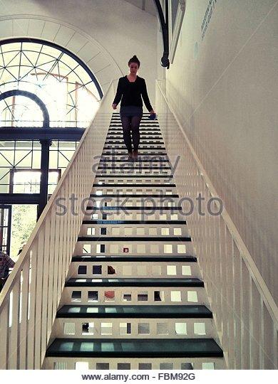 Junge Frau, die Treppe hinunter zu Hause bewegen Stockbild