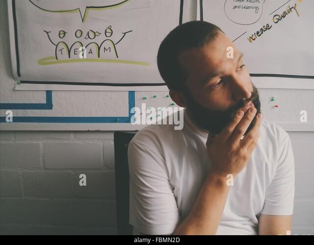 Mann auf Stuhl sitzend und wegschauen gegen Wand Stockbild