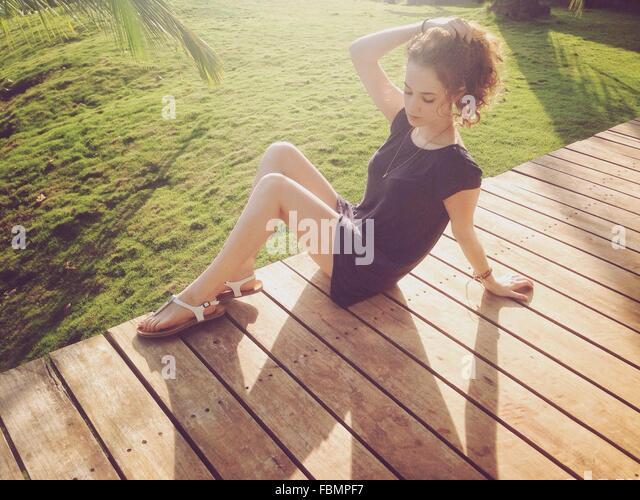 Schöne Frau auf der Suche nach unten sitzend auf Promenade Stockbild