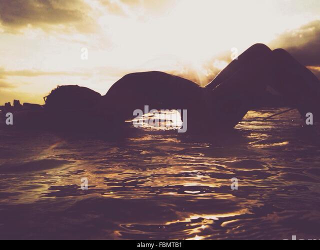 Silhouette der Frau im Wasser liegend Stockbild