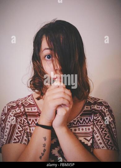 Porträt der Frau bedeckte Gesicht mit Haaren zu Hause Stockbild