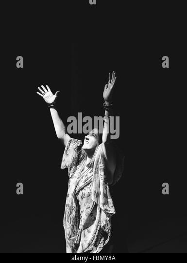 Junge Frau, die Hände erhebend auf schwarzem Hintergrund Stockbild