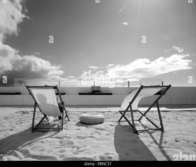Liegestühle auf Sand gegen bewölkten Himmel an sonnigen Tag Stockbild