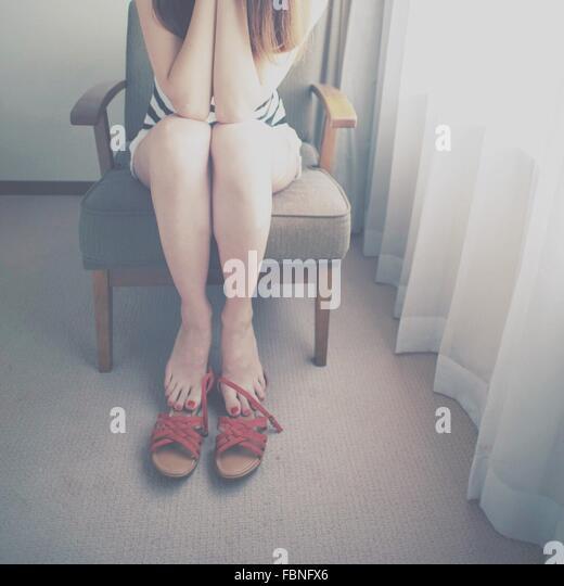 Frau auf einem Stuhl sitzend Stockbild