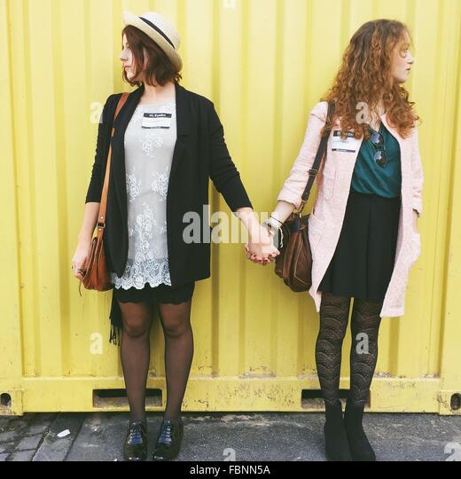 Junge Freundinnen Händchen beim wegsehen gegen Frachtcontainer Stockbild