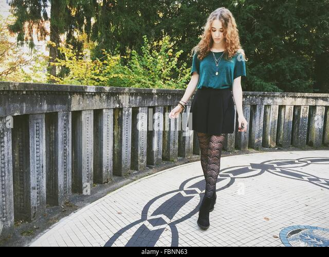 Schöne Frau auf der Suche nach unten während des Gehens auf Bürgersteig Stockbild