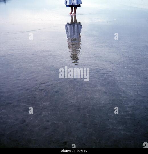 Geringer Teil der Frau zu Fuß auf dem Wasser mit Reflexion Stockbild