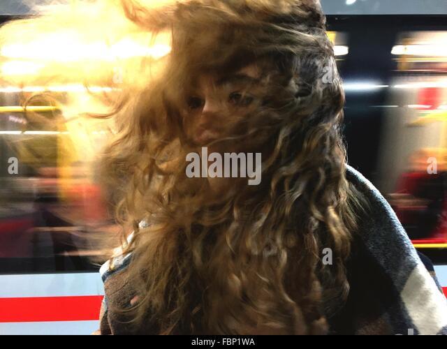 Junge Frau mit Wind fegte Haare am Bahnhof gegen Zug Stockbild